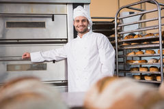 Happy baker leaning on professional oven Royalty Free Stock Photo