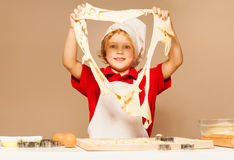 Happy baker looking through the big hole of dough. Young baker, boy in white apron and toque, looking through the big hole of dough, standing against the Royalty Free Stock Photo