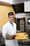 Happy baker showing his baguettes in his bakery Royalty Free Stock Images
