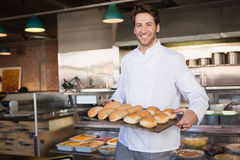 Happy baker showing tray with bread royalty free stock image