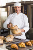 Happy baker showing tray of fresh bread Royalty Free Stock Photography