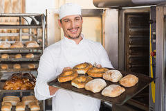 Happy baker showing tray of fresh bread Stock Photos