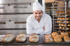 Happy baker standing near tray with bread. At the bakery Royalty Free Stock Photography