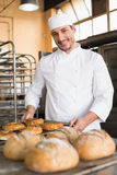 Happy baker taking out fresh bagels Stock Photography