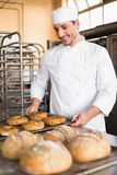 Happy baker taking out fresh bagels Stock Images
