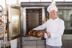 Happy baker taking out fresh bread Royalty Free Stock Photography