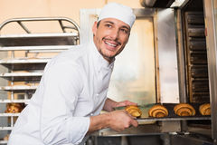 Happy baker taking out fresh croissants Royalty Free Stock Photography