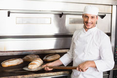 Happy baker taking out fresh loaf Royalty Free Stock Photos