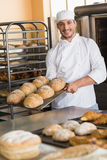 Happy baker taking out fresh loaves Royalty Free Stock Image