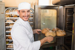 Happy baker taking out fresh loaves. In the kitchen of the bakery Stock Photography