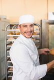 Happy baker taking out fresh loaves Stock Image