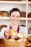 Happy bakery worker selling fresh rolls stock photos
