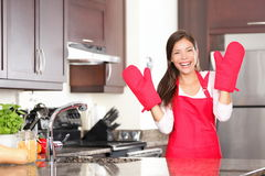 Happy baking cooking woman. Standing in her new kitchen smiling cheerful wearing apron and oven mitts ready to bake. Beautiful young mixed race Caucasian / Stock Photos