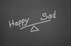 Happy Balance. Blackboard with a happy and sad balance Seesaw Stock Photo
