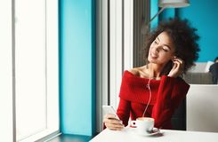 Happy balck girl at cafe listening to music. Happy smiling black girl at cafe table listening to music on smartphone. Young woman enjoying hot coffee and Stock Photos