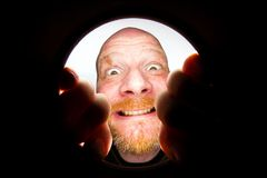 Happy bald man looking down a hole. A funny looking bald man with a red beard looking down a dark hole Stock Images