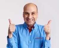 Happy bald man showing thumbs up. Isolated. Funny guy. Happy bald man showing thumbs up. Isolated on grey. Studio shot Royalty Free Stock Image