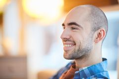 Handsome guy. Happy bald man with toothy smile looking forwards while relaxing or thinking of something Royalty Free Stock Photos