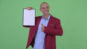 Happy bald multi ethnic businessman showing clipboard and giving thumbs up. Studio shot of handsome bald multi ethnic businessman against chroma key with green stock footage
