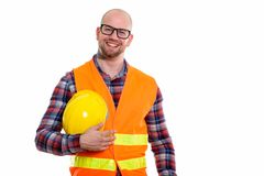 Young bald muscular man construction worker. Happy bald muscular man construction worker smiling while holding safety helmet Royalty Free Stock Images
