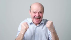 Happy bald senior man in shirt celebrating his success over gray background. stock video footage