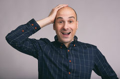Happy bald young man shoked. Isolated on gray background Stock Image