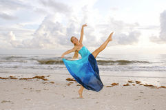 Happy ballerina on beach. A beautiful adult female ballerina with a big smile is dancing on the beach with her leg kicked up high looking at you the viewer with Stock Images