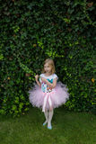 Happy ballerina in pink tutu stretching her hands and doing exercise on the green grass before dance Stock Photography