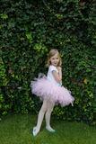 Happy ballerina in pink tutu stretching her hands and doing exercise on the green grass before dance Royalty Free Stock Photography