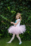 Happy ballerina in pink tutu stretching her hands and doing exercise on the green grass before dance Royalty Free Stock Photos