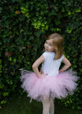 Happy ballerina in pink tutu stretching her hands and doing exercise on the green grass before dance Royalty Free Stock Image