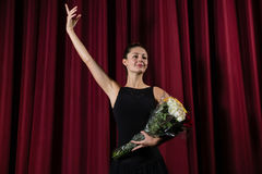 Ballerina posing with flower bouquet on stage Royalty Free Stock Photos