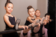 Happy ballet dancer during class. Cute little girl loving her ballet class and raising her leg on a ballet barre stock image