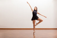 Happy ballet dancer in a studio. Cute female ballet dancer standing on the tip of her toes and smiling in a studio Stock Image