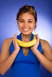 Happy Banana. Cute Girl Smiling and Holding Bananas against Blue Background Stock Images