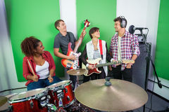 Happy Band Members Performing Together. In recording studio Royalty Free Stock Photography