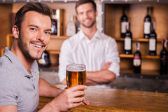 Happy bar customer. Happy bar customer holding glass of beer and smiling while bartender standing in the background stock photography