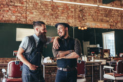Happy barber with client standing at barbershop. Shot of happy barber with client standing at barbershop and smiling. Two men at salon, hairstylist and customer stock photography