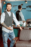 Happy barber leaning on a chair Stock Image