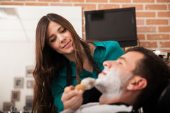 Happy barber shaving a client Stock Images
