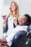 Happy barber and smiling customer in salon stock photos