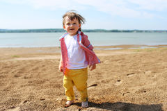 Happy barefoot baby walking on riverside Stock Images