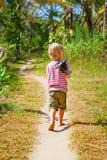 Happy barefoot child walk alone on beach by jungle path stock photos