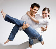 Happy barefoot man carrying wife in his arms Stock Images