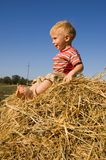 Happy barefooted baby boy sit on a hayrick. Smiling barefooted little boy sit on a hayrick against country landscape and blue sky royalty free stock photo