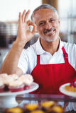 Happy barista looking at camera and gesturing ok sign Stock Images