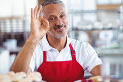Happy barista looking at camera and gesturing ok sign Stock Photography