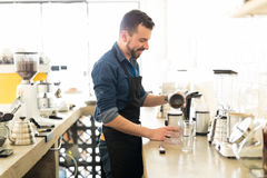 Happy barista making a cup of coffee. Profile portrait of a handsome Hispanic barista grinding some coffee grains and loving his job Stock Photos