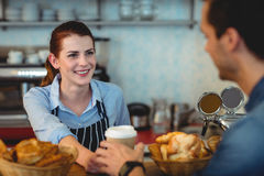 Happy barista offering coffee to customer at cafe. Happy female barista offering coffee to customer at cafe Royalty Free Stock Images
