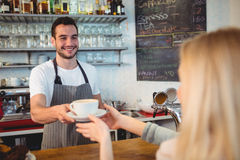 Happy barista serving coffee to woman at cafe. Happy young barista serving coffee to woman at cafe Royalty Free Stock Photography